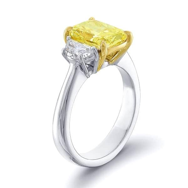 three stone diamond ring with yellow fancy elongated cushion and two half moon cut diamonds
